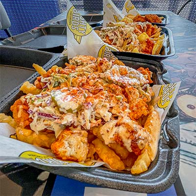 Three to-go plates of hot chicken and fries with topping and sauce from lunch restaurant in Lynwood CA.